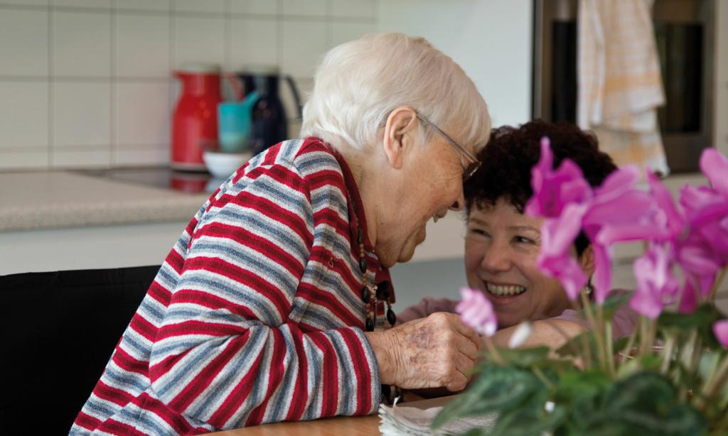 Zwei ältere Frauen lachen sich an einem Tisch an. Im Vordergrund Blumen.