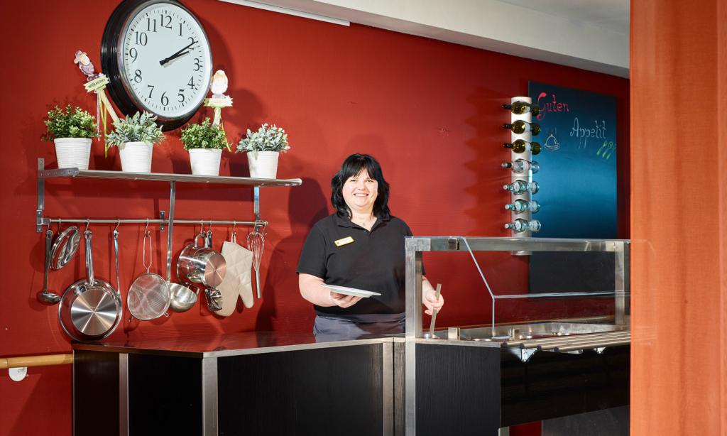 Mitarbeiterin steht hinter der Theke in der Cafeteria. Im Hintergrund Uhr, Pflanzen und Kochutensilien